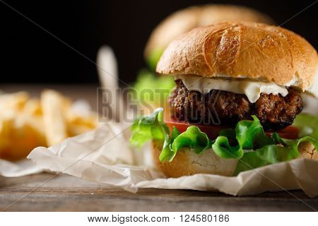 Homemade tasty burger and french fries on wooden table