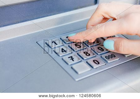 Ladies hand dials the PIN code at an ATM close-up