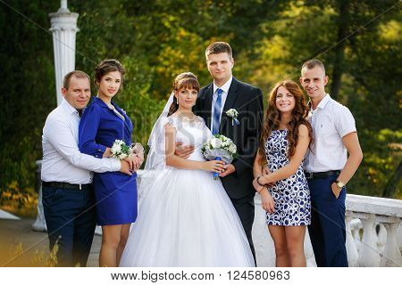 portrait of newlywed couple with bridesmaids and groomsmen in green sunny park ** Note: Soft Focus at 100%, best at smaller sizes