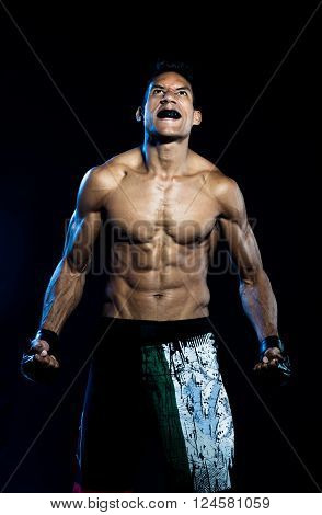 Furious fighter man screaming on Black Background
