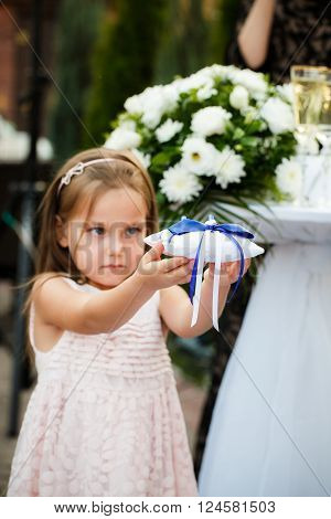 The girl holds a pillow with wedding rings during a wedding ceremony