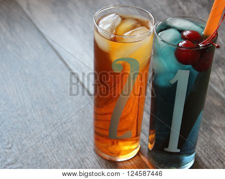 Numbers 2 & 1 printed on two tall glasses filled with colorful cocktail glasses with room for copy