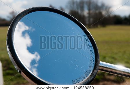 Rear view mirror of a motorcycle with clouds in view