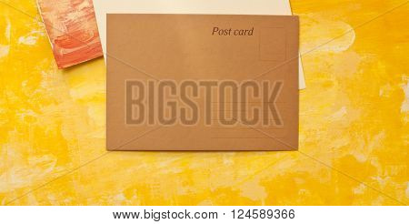 A brown paper blank postcard with a place for text shot from above on painterly textures; the golden yellow page has additional copyspace