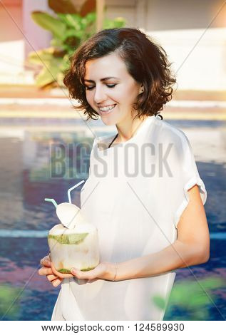 Young and happy woman drinks fresh coconut with strobe, Photo with light flare.