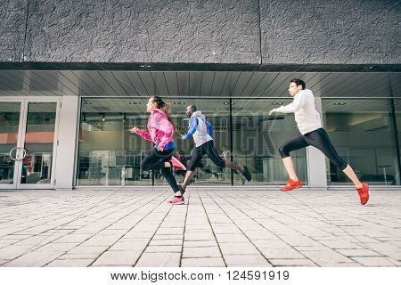 Three runners sprinting outdoors - Sportive people training in a urban area healthy lifestyle and sport concepts