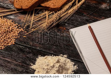 Spikelets of wheat and rye bread on a wooden table