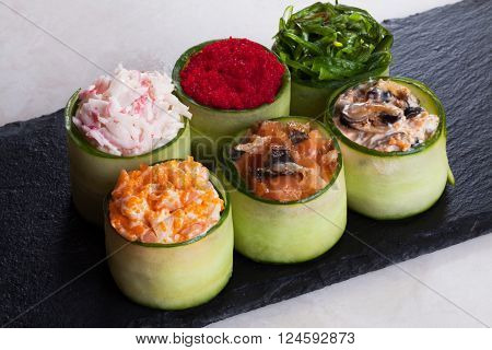 Assorted sushi wrapped in cucumber large masago, shrimp, salmon, crab, Chuka, the six pieces on the graphite board
