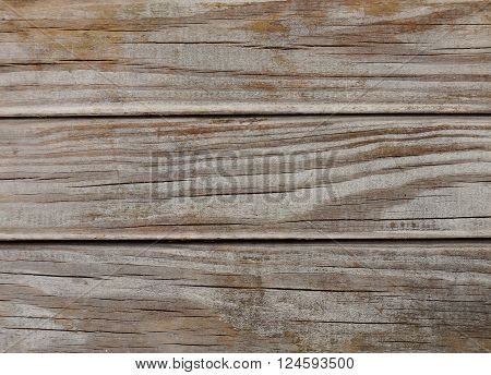 Macro of strongly weathered wood. Naturally aged by the elements. Horizontal cracks can be seen in the well dried wood. The color is partially worn away and shows the grain of the wood. The macro shows three horizontal planks.