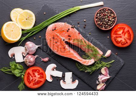 red fish steak with spices and vegetables on a slate table.