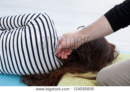 Reflexology. Man's hand manipulates on the woman's neck by the knuckles woman lays on the mat