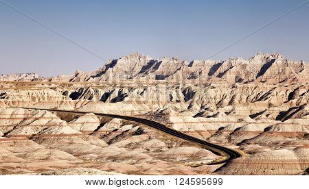 Scenic landscape image of the Badlands of South Dakota, on a warm autumn day, with clear blue sky.  Interior highway pictured.