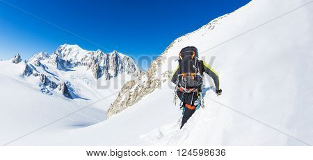 Mountaineer climbs a snowy peak. In background the glaciers and the summit of Mont Blanc, the highest european mountain. The Alps, Chamonix, France, Europe.