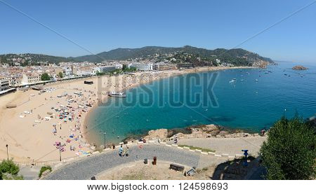 TOSSA DE MAR, CATLONIA, SPAIN - JUNE 19: Resort vacationers are visiting Platja Gran beach near fortress Vila Vella enceinte on June 19, 2014 in Tossa de Mar, Costa Brava, Catalonia, Spain.