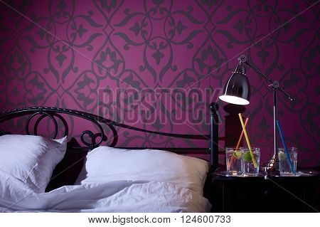 Bed chamber. Cocktails on night stand near bed with light on. Black floral pattern on purple wall. Concept of late night drinks.