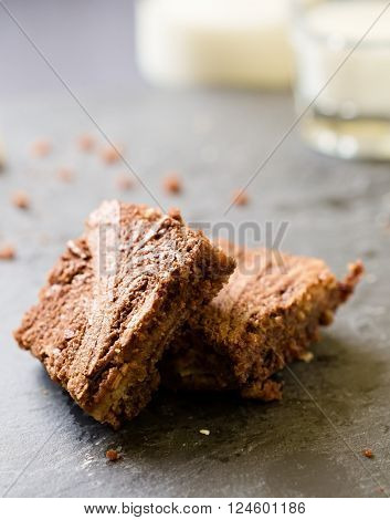 Marble cake brownies on top of each other with milk glass andmilk bottle in background. Selecitive focus.