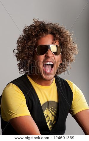 Cheerful young man with beautiful curls have fun