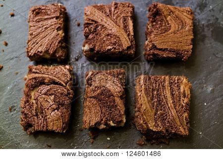 Marble cake brownies on stone slate dark background. Flat lay. Top down.