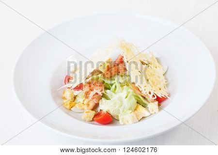Caesar salad with grilled chicken and parmesan crisps on a plate on top of a white background isolated beautiful series menu