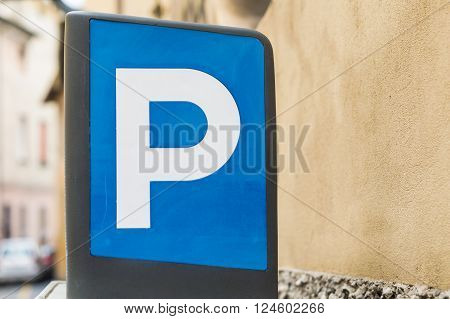 Blue parking sign with blurred cars on the left and empty space on the right