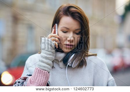 Young woman talk over her mobile, portrait taken on the street, urban background
