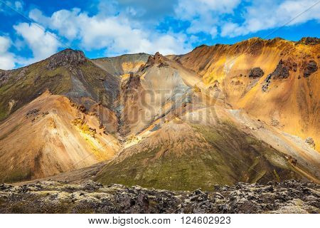 Multi-colored mountains from rhyolite are lit with the July sun. Travel to Iceland in the summer. National park Landmannalaugar