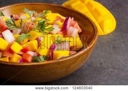 Homemade Mango salsa served in a wooden plate