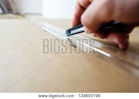 Man cutting with sharp cutter knife a cardboard box to open it before installing furniture