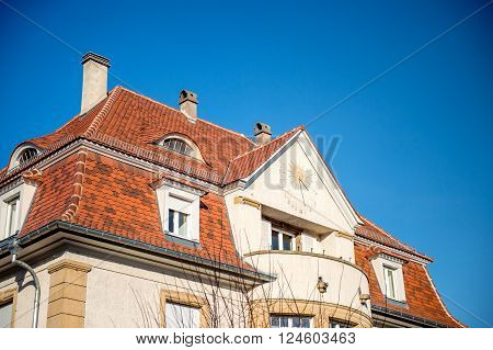 Side view of astronomical clock in on the facade of a house on a clear sky day
