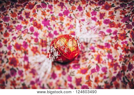 KILCHBERG SWITZERLAND - MARCH 20 2014: Lindt Lindor chocolate truffle on a red luxury floral background. Lindt is one one of the lastgest luxury chocolate and confectionery company worldwide with more than 30 factories worldwide