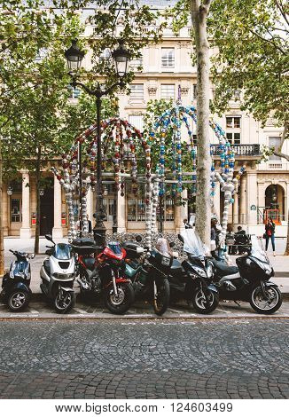 PARIS FRANCE - AUG 18 2014: Le Kiosque des Noctambules artistic roof in the center of Paris located in Place Colette with multiple motorcycles parked in front
