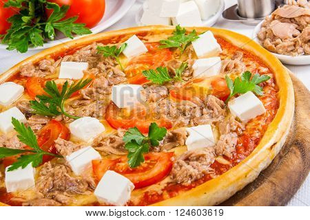 Pizza with tuna, tomato, cheese on wooden board