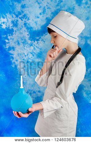 Kid in white doctor costume and stethoscope holding blue medical enema on blue background