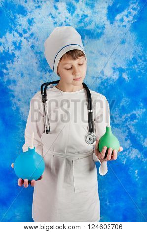 Cute boyin white medicine costume holding blue and green enemas in hands on blue background