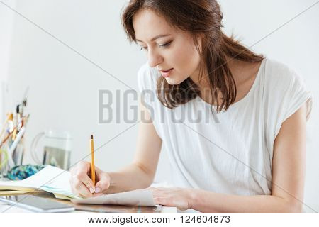 Attractive focused woman artist making sketches in workshop