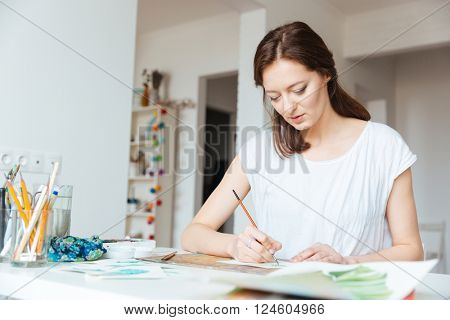 Beautiful inspired woman painter sitting and painting in art studio