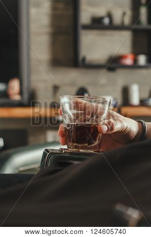 Male Hand Holding A Glass Of Whiskey While Sitting In Chair At Barbershop. Barbershop Theme