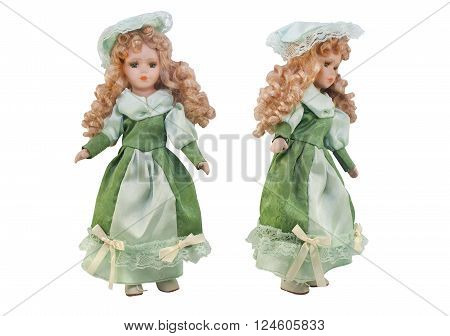 Isolated photo of old-fashioned doll in green dress with hat and curly hair on white background.