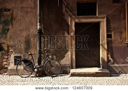 Bicycle standing next to an old wall and door in European city