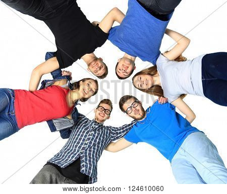 portrait of confident college students forming huddle over white background