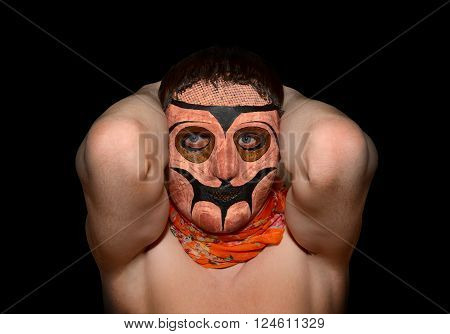 man in terrible mask with her ??hands behind her head on a black background