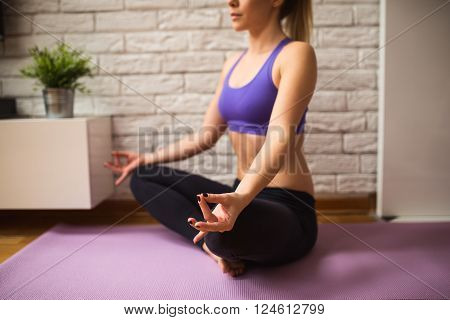 Woman doing yoga meditation at home. Selective focus on the closer hand
