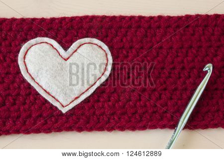 Different crochet crafts on a wooden background.