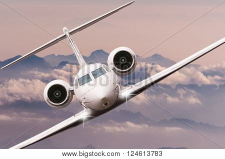 Airplane flying over clouds and Alps mountain on sunset. Front view of a big passenger or cargo aircraft, business jet, airline. Transportation and travel concept.