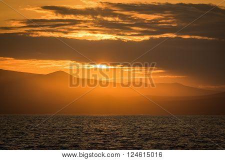 Orange dawn over hilly coastline and ocean
