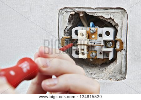 Replacing damaged light switch, disassembly of the old appliance close-up.