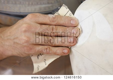 sanding white marble, up close hand and pice of sandpaper