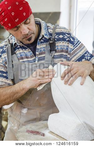 sculptor polish white marble with sandpaper in a studio