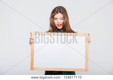 Pretty casual woman holding blank board and winking isolated on a white background
