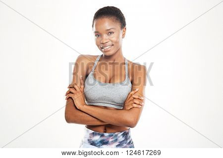 Portrait of happy beautiful young african american sportswoman standing with arms crossed over white background